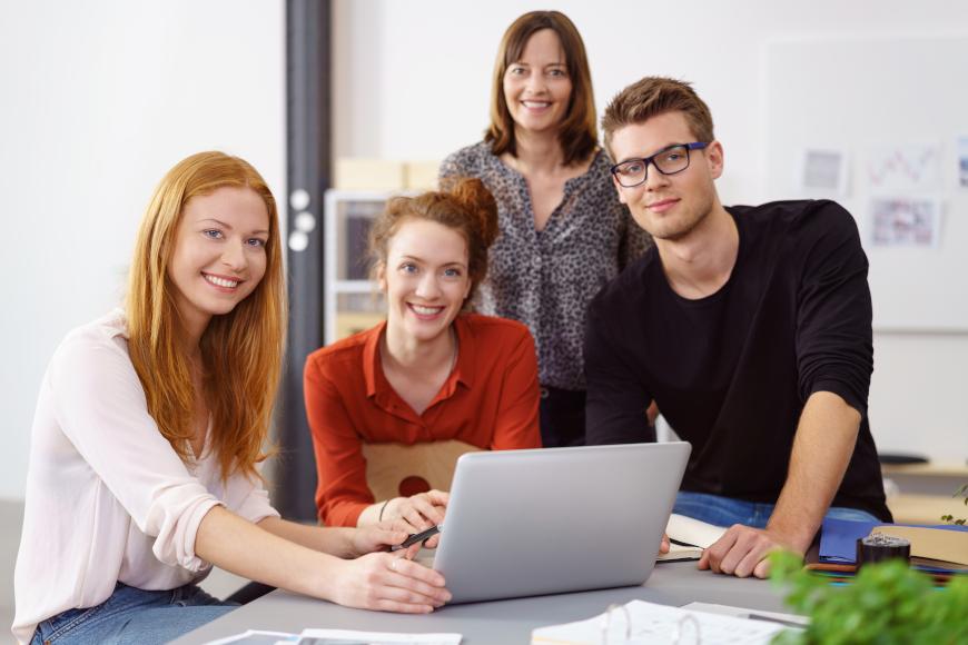 nasmiješeni učenici sjede ispred laptopaa