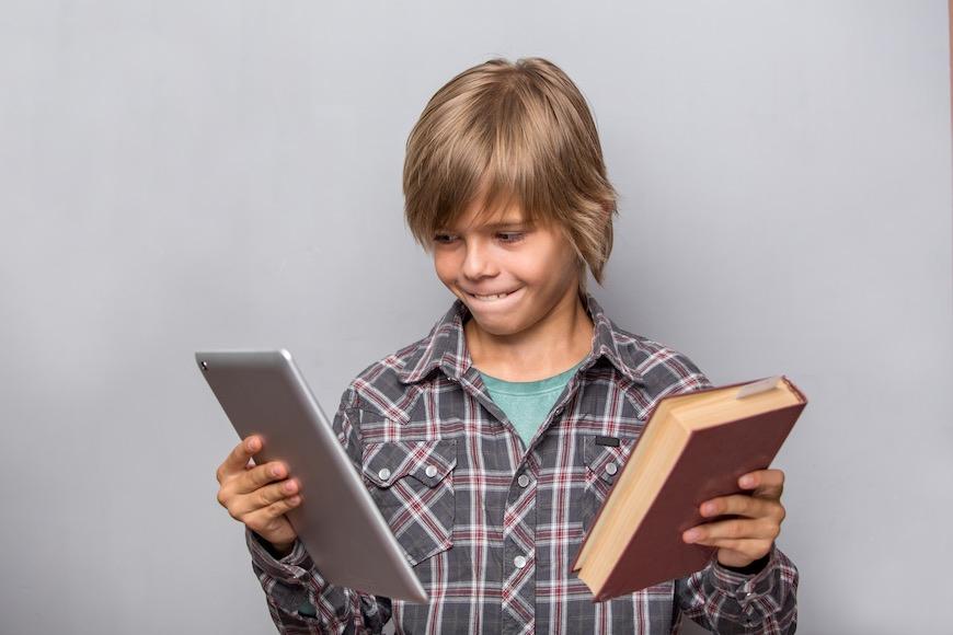 učenik u rukama drži tablet i knjigu
